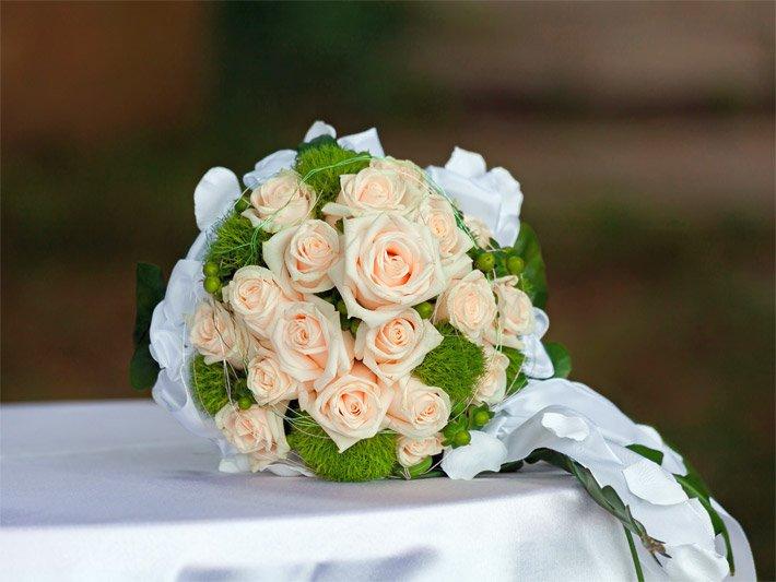 Foto von einem Brautstrauß mit blass-orangen Rosen und dekoriert mit ...