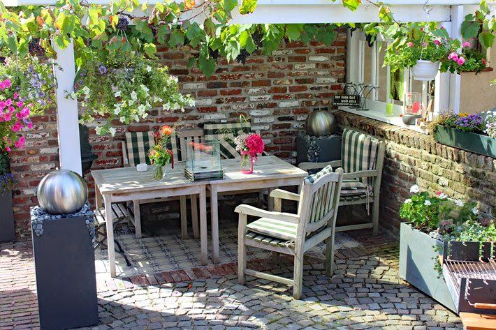 Terrasse Mit Holztisch Und Stühlen, Dekoriert Mit Verschiedenen Blumen  Töpfen